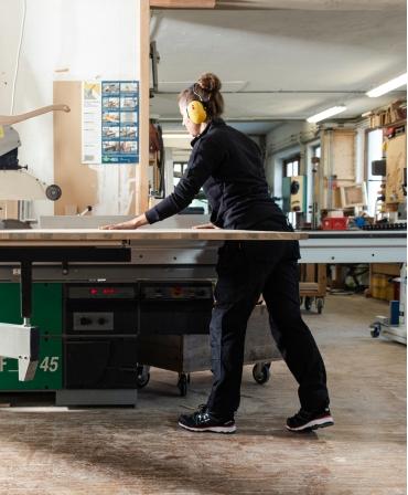 Pantaloni de lucru dama Helly Hansen Luna Construction, negri, la bancul de lucru cu lemn
