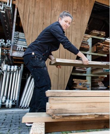 Pantaloni de lucru dama Helly Hansen Luna Construction, negri, imbracati, in timpul lucrului, vedere laterala