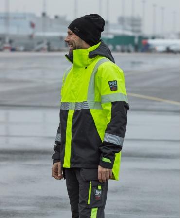 Geaca de iarna cu gluga Helly Hansen ICU Winter, impermeabila, reflectorizanta, HVC2, 3, galben/negru, imbracata din profil