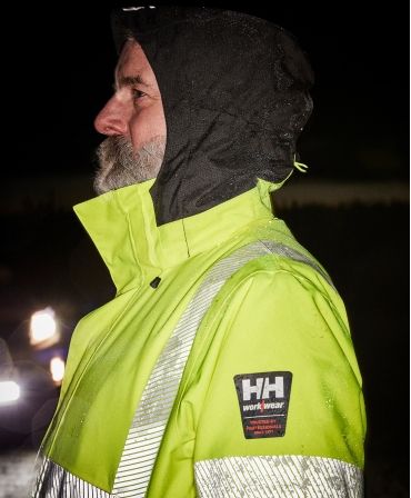 Geaca de iarna cu gluga Helly Hansen ICU Winter, impermeabila, reflectorizanta, HVC2, 3, galben/negru, profil in timpul noptii